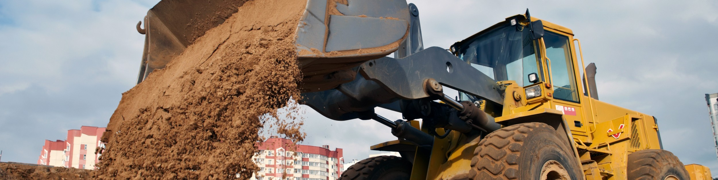 Wheel loader machine unloading sand at eathmoving works in construction site. Stock photoFile #: 13818199